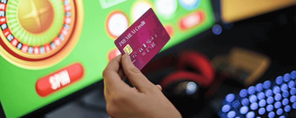 Kreditkarte mit Roulette am Bildschirm im Hintergrund
